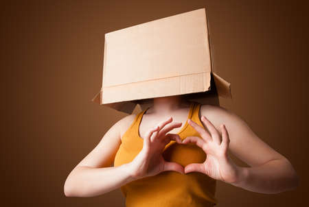 masquerader: Young girl standing and gesturing with a cardboard box on his head