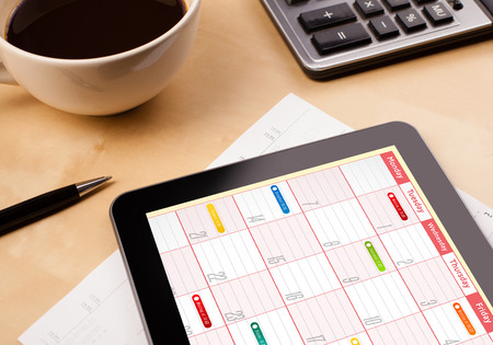 Workplace with tablet pc showing calendar and a cup of coffee on a wooden work table close-up photo