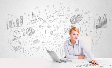 Business woman at desk with hand drawn charts at the background photo
