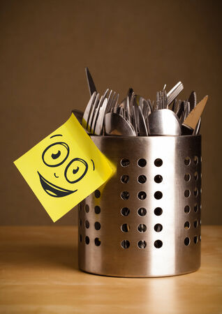 Drawn smiley face on a sticky note sticked on a cutlery case photo