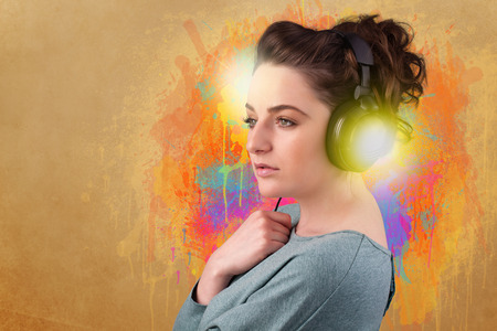 Pretty young woman with headphones listening to music in front of a painted wall photo