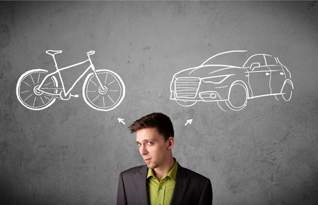 Young businessman taking a decision between bicycle and car photo