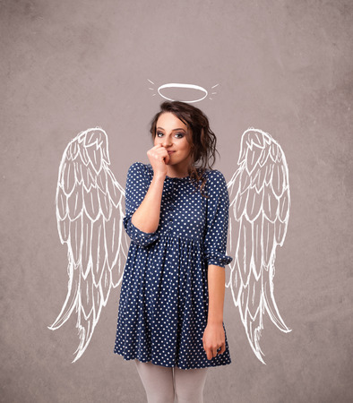 Cute girl with angel illustrated wings on grungy wall photo
