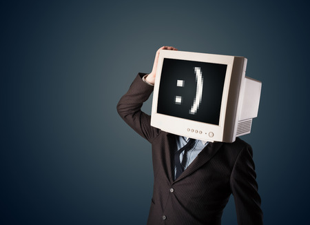 Funny young businessman with a monitor on his head and smiley on the black screen photo