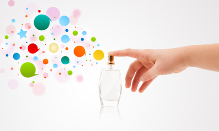 close up of woman hands spraying colorful bubbles from beautiful perfume bottle