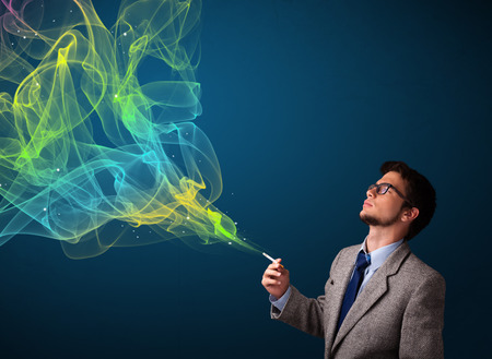 cigare: Handsome young man smoking cigarette with colorful smoke