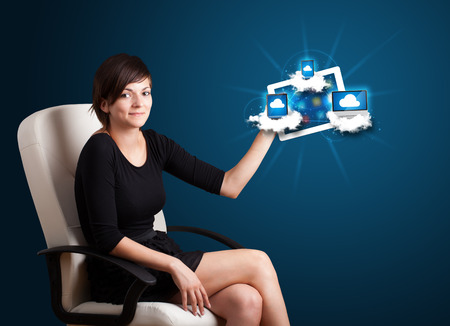 Beautiful young woman holding tablet with modern devices in clouds photo