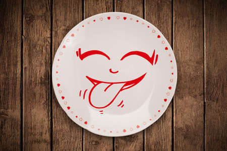 Happy smiley cartoon face on colorful dish plate and grungy wall photo