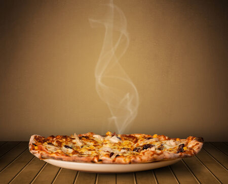 home cooked: Fresh delicious home cooked pizza with steam on wood deck Stock Photo