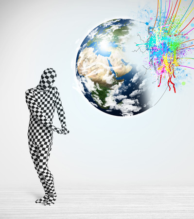 Funny man in body suit looking at colorful splatter 3d earth photo