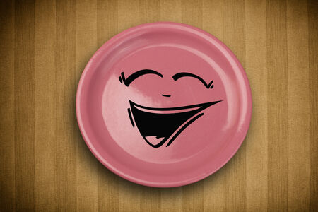 Happy smiley cartoon face on colorful dish plate and grungy table  photo