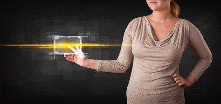 Tech woman touching button with orange light beams concept  photo
