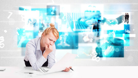 Business person at desk with modern blue tech images at background photo