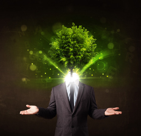 Man with green tree head concept on brown  photo