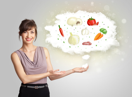 Pretty woman presenting a cloud of healthy nutritional vegetables concept photo