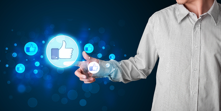 Young person pressing thumbs up button on modern social network system photo