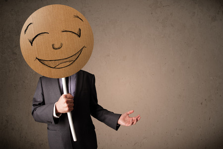happiness concept: Businessman holding a cardboard smiley face emoticon in front of his head Stock Photo