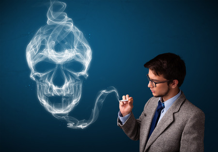 Handsome young man smoking dangerous cigarette with toxic skull smoke Stock Photo - 26564036