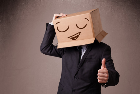 masquerader: Businessman standing and gesturing with a cardboard box on his head with smiley face Stock Photo