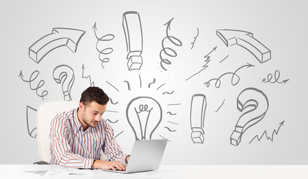 Good-looking young businessman brainstorming with drawn arrows and symbols photo