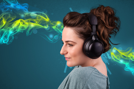 Pretty young woman with headphones listening to music, glowing smoke concept photo