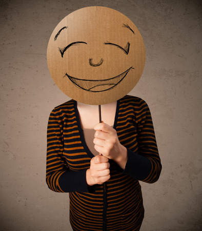 Young lady holding a cardboard smiley face emoticon in front of her head photo