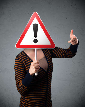 Young woman holding a red traffic triangle warning sign in front of her head Stock Photo - 26399049