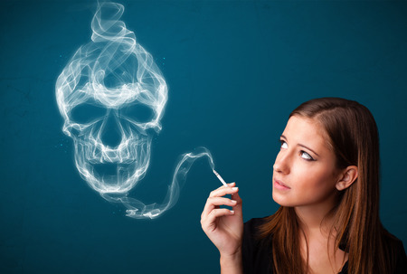Pretty young woman smoking dangerous cigarette with toxic skull smoke Stock Photo - 26430661