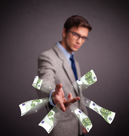 Handsome young man standing and throwing money Stock Photo - 26430771