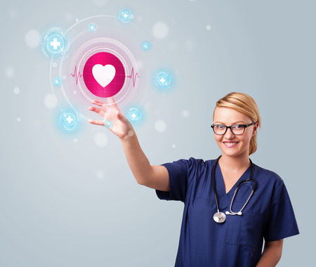 first finger: Young nurse standing and pressing modern medical type of buttons Stock Photo