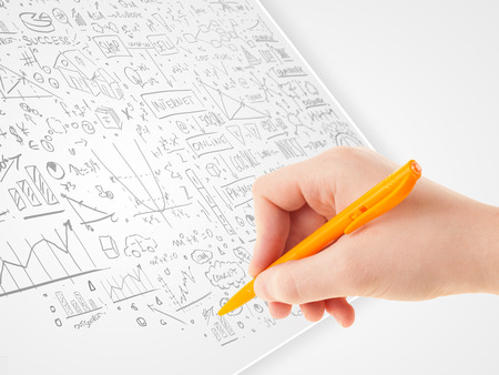Human hand sketching multiple ideas on a paper photo