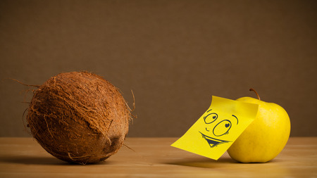 reacting: Apple with sticky note reacting at coconut