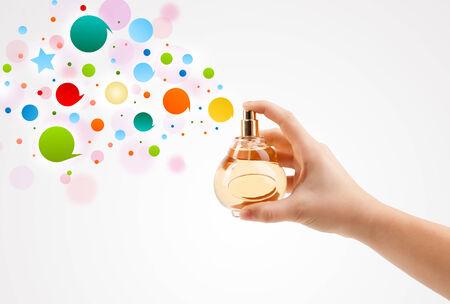 아름 다운 향수 병에서 다채로운 거품을 살포하는 여자 손 가까이