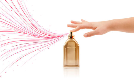 close up of woman hands spraying colorful lines from beautiful perfume bottle photo