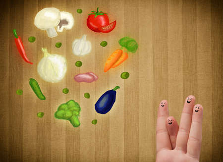 cheerfully: Happy smiley face fingers cheerfully looking at illustration of colorful healthy vegetables Stock Photo