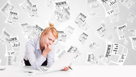 Business woman at desk with stock market newspapers concept photo