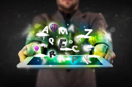 Young person showing white tablet with abstract letters and sky photo
