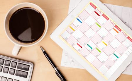 Poste de travail avec tablette pc montrant calendrier et une tasse de café sur une table de travail en bois close-up