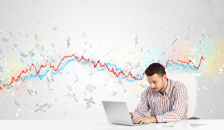 stock news: Business man sitting at table with stock market graph 3d letters