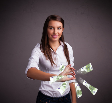 Pretty young woman standing and throwing money photo