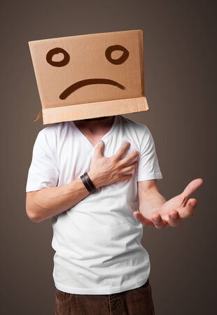 boxy: Young man standing with a brown cardboard box on his head with sad face Stock Photo