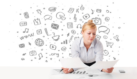 Beautiful young businesswoman with all kind of hand-drawn media icons in background photo