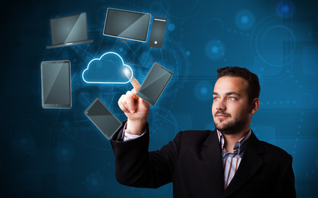 Attractive young businessman touching high technlogy cloud service Stock Photo