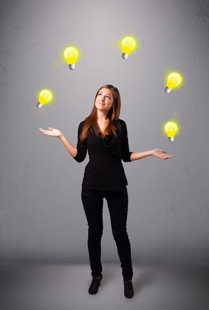 juggling: beautiful young lady standing and juggling with light bulbs