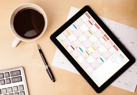 Lugar de trabajo con PC de la tableta de calendario que muestra y una taza de café en una mesa de trabajo de madera de cerca