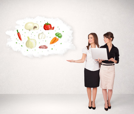 piramide nutricional: Las chicas j�venes que presentan nube nutricional con verduras concepto Foto de archivo
