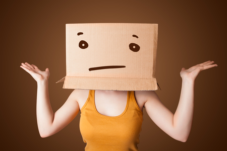 masquerader: Young girl standing and gesturing with a cardboard box on her head with straight face