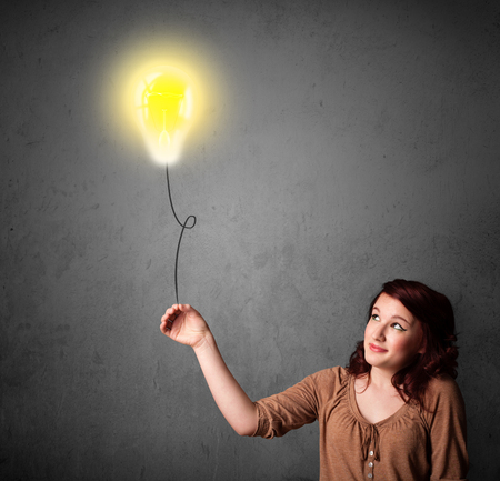 Young woman holding a lightbulb balloon photo