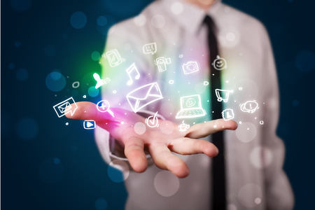 Young business man in suit presenting colorful glowing social media icons photo