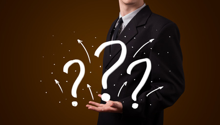 Young business man in suit presenting hand drawn question marks photo